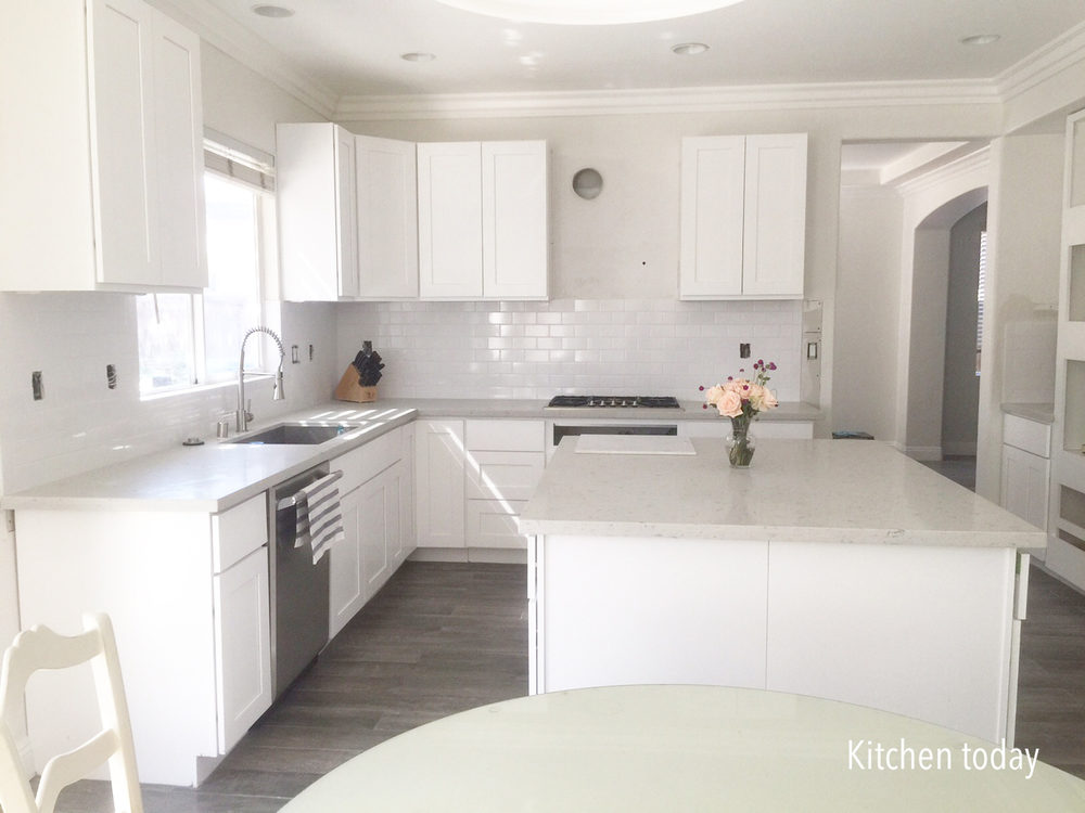 White shaker cabinets (still missing pulls & glass doors) with light gray quartz countertop